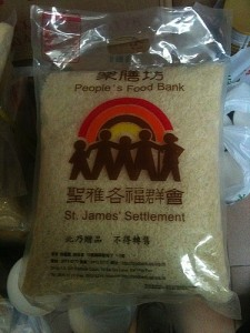 """The Food Bank Repacks Rice in """"St. James Settlement People's Food Bank"""" Bags"""